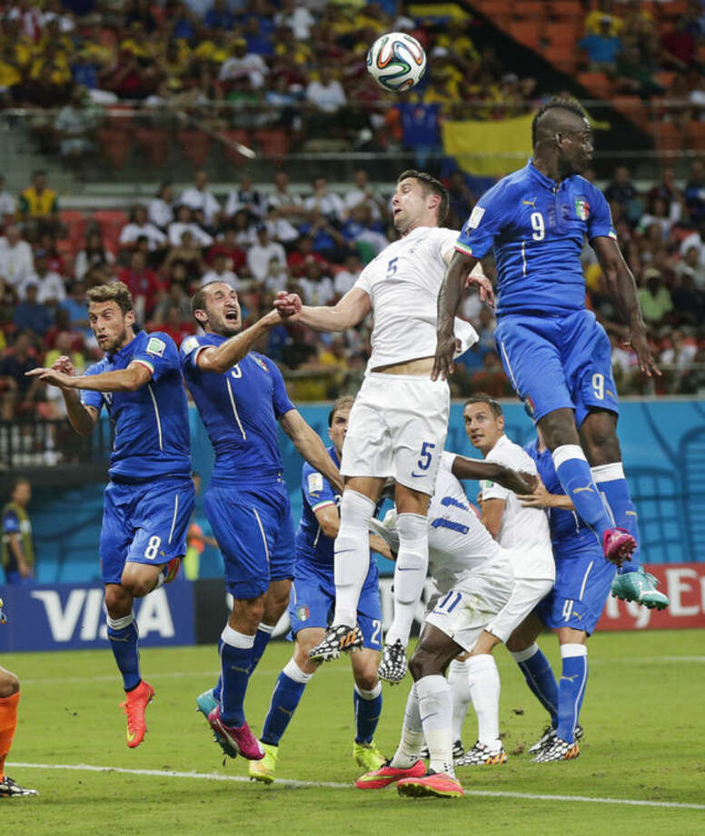 England's Gary Cahill (5) goes up to head the ball against Italy's Mario Balotelli (9) during the group D World Cup soccer match between England and Italy at the Arena da Amazonia in Manaus, Brazil, Saturday, June 14, 2014. (AP Photo/Marcio Jose Sanchez)