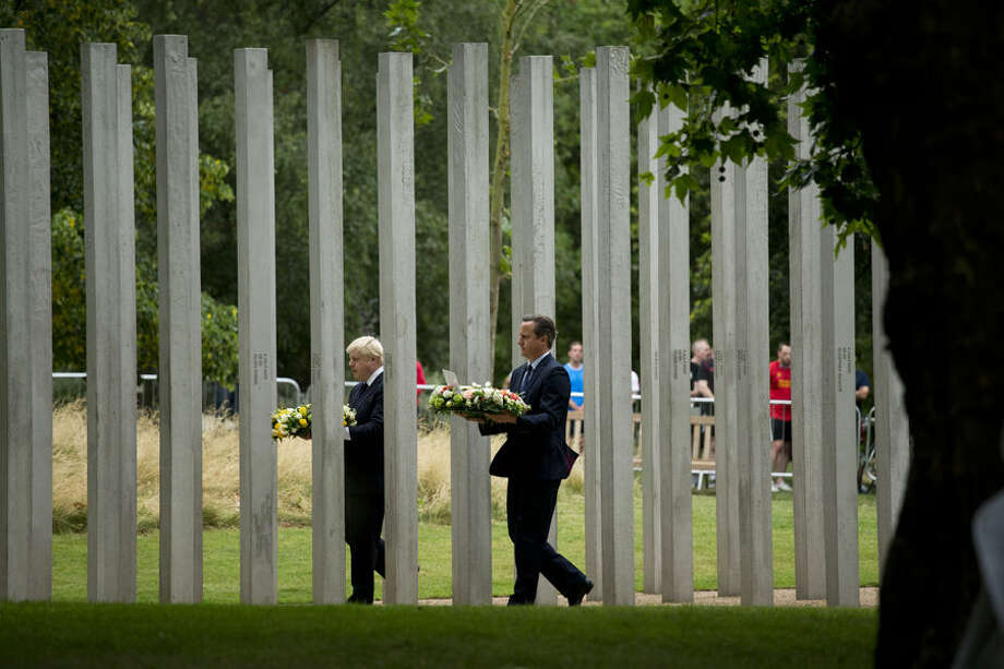 Britain's Prime Minister David Cameron, right, and London Mayor Boris Johnson walk through the 7/7 memorial in Hyde Park to lay wreaths in London, Tuesday, July 7, 2015. Britons marked the 10th anniversary of suicide bomb attacks on London's transit system Tuesday, as Prime Minister David Cameron said the recent slaying of 30 British tourists in Tunisia was a reminder that terror threats remain real and deadly. (AP Photo/Matt Dunham)