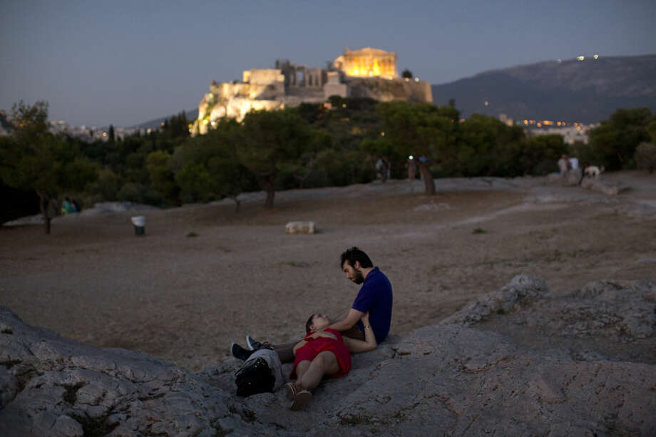 A couple sit in front of the ancient Acropolis hill, with the ruins of the fifth century BC Parthenon temple, in central Athens, Tuesday, July 7, 2015. (AP Photo/Emilio Morenatti)
