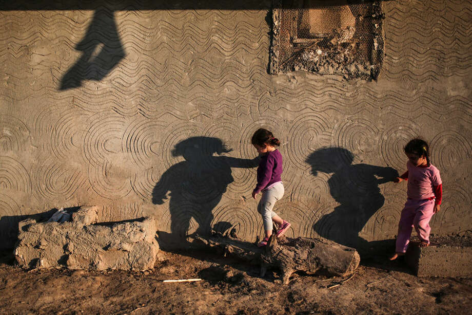 In this Wednesday, May 6, 2015 photo, the shadows of children are cast on the wall of their home in the Nile Delta town of Behira, 300 kilometers (186 miles) north of Cairo, Egypt. Urban growth has become the chief threat to farmland as Egyptian farmers haphazardly _ and illegally _ build new houses to make room for the next generation. (AP Photo/Mosa'ab Elshamy)