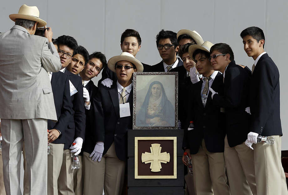 Faithful take their picture with an image of Our Lady of Sorrows prior to the start of Mass celebrated by Pope Francis at Bicentennial Park in Quito, Ecuador, Tuesday, July 7, 2015. Francis is making his first visit as pope to his Spanish-speaking neighborhood, traveling to three South American nations: Ecuador, Bolivia and Paraguay. (AP Photo/Gregorio Borgia)