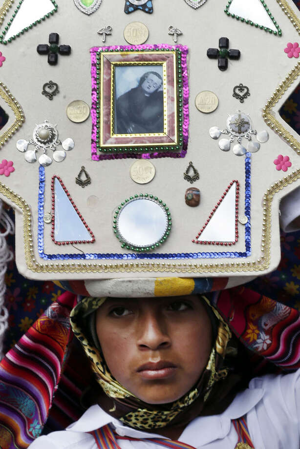 In this June 4, 2015 photo, a Pujili dancer wears a headdress decorated with Catholic and indigenous symbols, as he performs in the streets of Pujili, Ecuador, during the Corpus Christi celebrations, jointly honoring the Holy Communion, or Eucharist, and Inti, the ancient Inca sun god. While most of the region's native peoples identify themselves as Roman Catholic, some practice syncretic rituals that blend the church's traditional beliefs with native customs. (AP Photo/Dolores Ochoa)