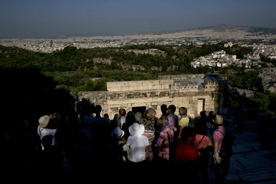 A group of tourist watch an aerial view of the city of Athens as they visit the ancient Acropolis hill, on Tuesday, July 7, 2015. Greek Prime Minister Alexis Tsipras was heading Tuesday to Brussels for an emergency meeting of eurozone leaders, where he will try to use a resounding referendum victory to eke out concessions from European creditors over a bailout for the crisis-ridden country. (AP Photo/Petros Giannakouris)