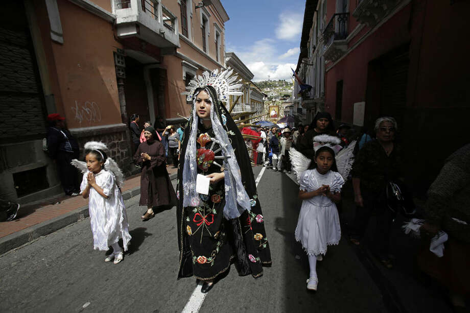 In this June 14, 2015 photo, a woman dressed as Our Lady of Sorrows takes part in a procession marking Ecuador's identity as a Catholic nation with its consecration to the Sacred Heart of Jesus in Quito. Pope Francis will encounter on his South American tour, indigenous people whose traditions date back centuries to even before European priests brought Christianity to the New World. (AP Photo/Dolores Ochoa)