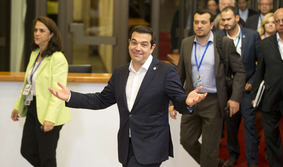 Greek Prime Minister Alexis Tsipras, center, leaves the building after an emergency summit of eurozone heads of state or government in Brussels on Tuesday, July 7, 2015. Frustrated and angered eurozone leaders gave Greek Prime Minister Alexis Tsipras a last-minute chance on Tuesday to finally come up with a viable proposal on how to save his country from financial ruin. (AP Photo/Michel Euler)
