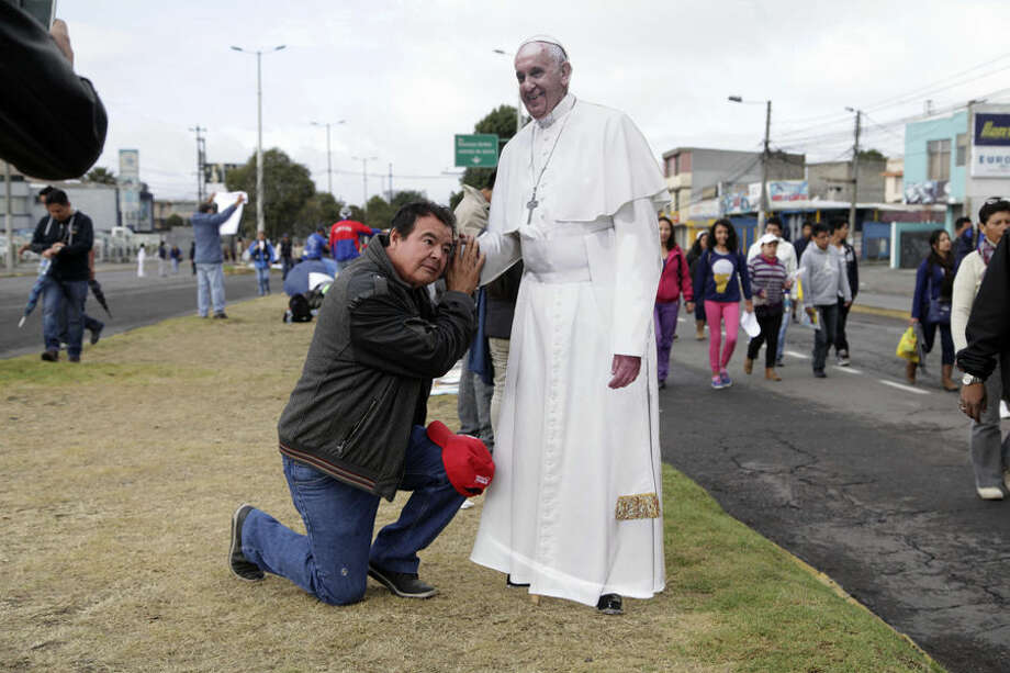 A man poses for a photo with a life-size cutout of Pope Francis at Bicentennial Park where the pontiff celebrated Mass in Quito, Ecuador, Tuesday, July 7, 2015. Francis is telling faithful in Ecuador that being model Catholics is the best form of evangelization. (AP Photo/Ana Buitron)