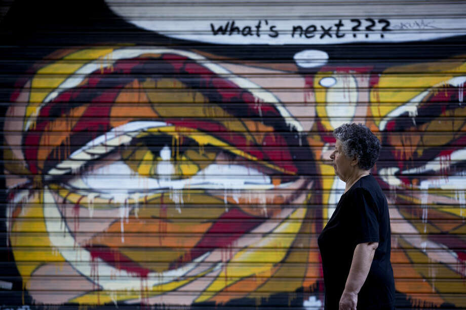 A woman walks past a graffiti in Athens, on Tuesday, July 7, 2015. Greek Prime Minister Alexis Tsipras was heading Tuesday to Brussels for an emergency meeting of eurozone leaders, where he will try to use a resounding referendum victory to eke out concessions from European creditors over a bailout for the crisis-ridden country. (AP Photo/Petros Giannakouris)