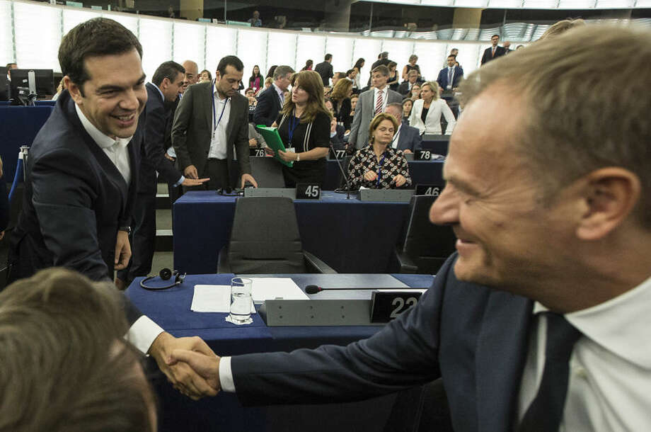 Greek Prime Minister Alexis Tsipras, left, shakes hands with Donald Tusk, president of the European Council, before delivering his speech at the European Parliament in Strasbourg, eastern France, Wednesday, July 8, 2015. Tsipras says his country wants a deal that will mean a definitive end to Greece's protracted financial crisis, and that last Sunday's referendum result does not mean a break with Europe. (AP Photo/Jean-Francois Badias)