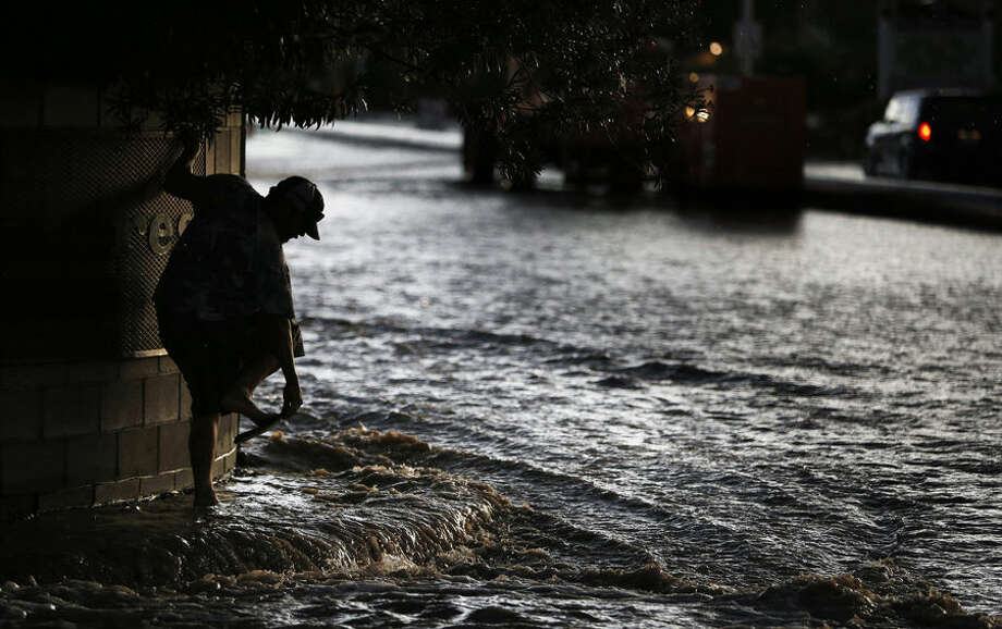 A man adjusts his sandals while wading through floodwater Monday, July 6, 2015, in Las Vegas. Heavy rain throughout the area prompted the National Weather Service to issue a flash flood warning for parts of Las Vegas. (AP Photo/John Locher)