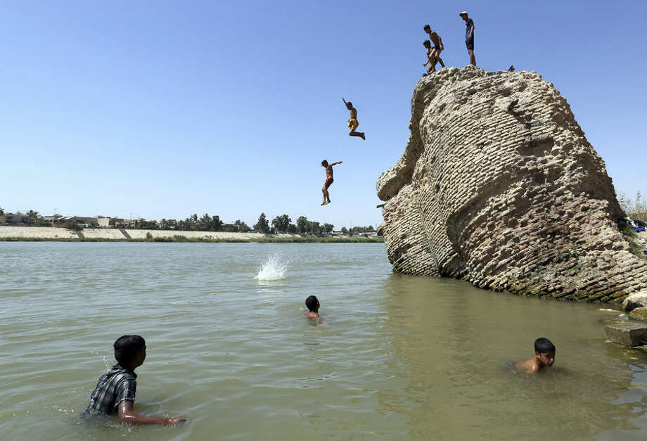 Children jump off the ruin of an old building into the Tigris River to beat the heat in Baghdad, Iraq, Tuesday, July 7, 2015. (AP Photo/Hadi Mizban)