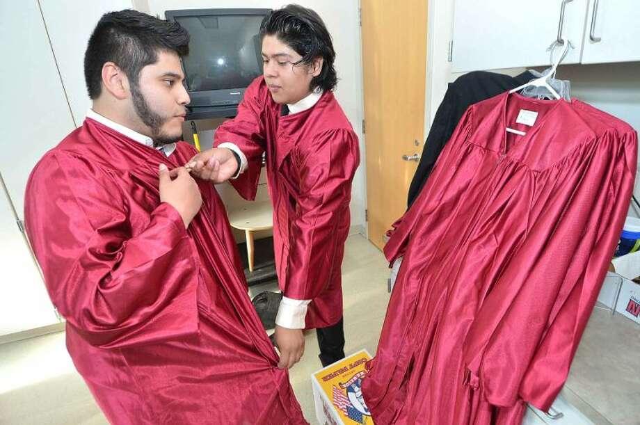 Hour Photo/Alex von Kleydorff Angel Buceta and Elvin Martinez help each other with their gowns at Briggs High School Class of 2014 Graduation
