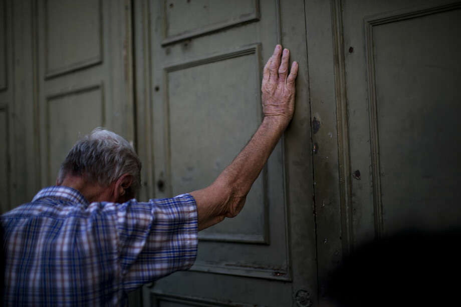 A pensioner leans against the main gate of the national bank of Greece as he waits to withdraw a maximum of 120 euros ($134) for the week in Athens in central Athens, Tuesday, July 7, 2015. Greek Prime Minister Alexis Tsipras heads Tuesday to Brussels, where he will try to use a bailout referendum victory to obtain a rescue deal with European leaders. (AP Photo/Emilio Morenatti)