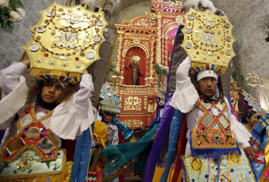 In this June 4, 2015 photo, a group of dancers perform on the main altar of the Catholic church in Pujili, Ecuador, showing gratitude to the Inca Sun God, Inti, the harvest, as well as celebrating the Holy Communion. While most of the region's native peoples identify themselves as Roman Catholic, some practice syncretic rituals that blend the church's traditional beliefs with native customs. Many Andean people see no contradiction in it. (AP Photo/Dolores Ochoa)