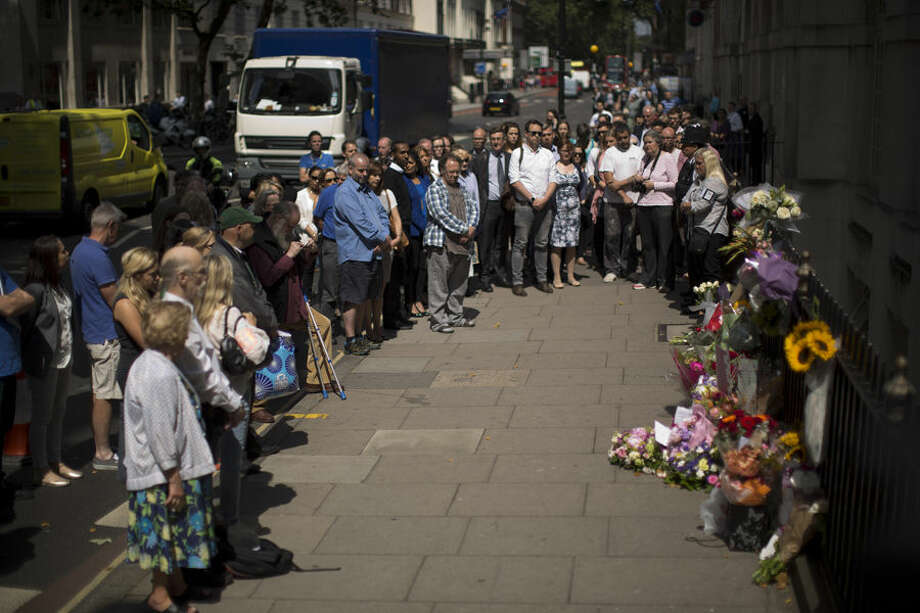 People stand together just before the start of a nationwide minute's silence on the 10 year anniversary of the 7/7 London attacks which killed 52 people, facing in the direction of a plaque and flowers laid at the location of where a suicide bomber blew themselves up during the morning rush hour on a bus in Tavistock Square, London, Tuesday, July 7, 2015. Britons marked the 10th anniversary of suicide bomb attacks on London's transit system Tuesday, as Prime Minister David Cameron said the recent slaying of 30 British tourists in Tunisia was a reminder that terror threats remain real and deadly. (AP Photo/Matt Dunham)