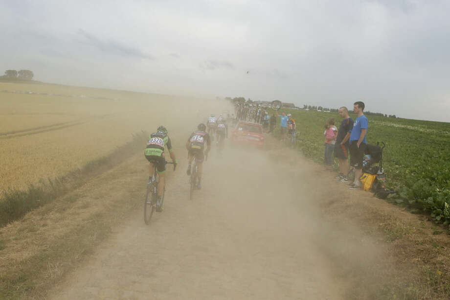 The pack disappears in a cloud of dust kicked up by riders, motorcycles and cars on a cobblestone sector during the fourth stage of the Tour de France cycling race over 223.5 kilometers (138.9 miles) with start in Seraing, Belgium, and finish in Cambrai, France, Tuesday, July 7, 2015. (AP Photo/Laurent Cipriani)