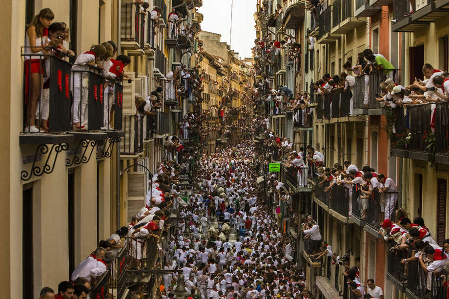 People watch as Jandilla fighting bulls and revelers run during the running of the bulls at the San Fermin festival in Pamplona, Spain, Tuesday, July 7, 2015. Revelers from around the world arrive to Pamplona every year to take part in some of the eight days of the running of the bulls. (AP Photo/Andres Kudacki)