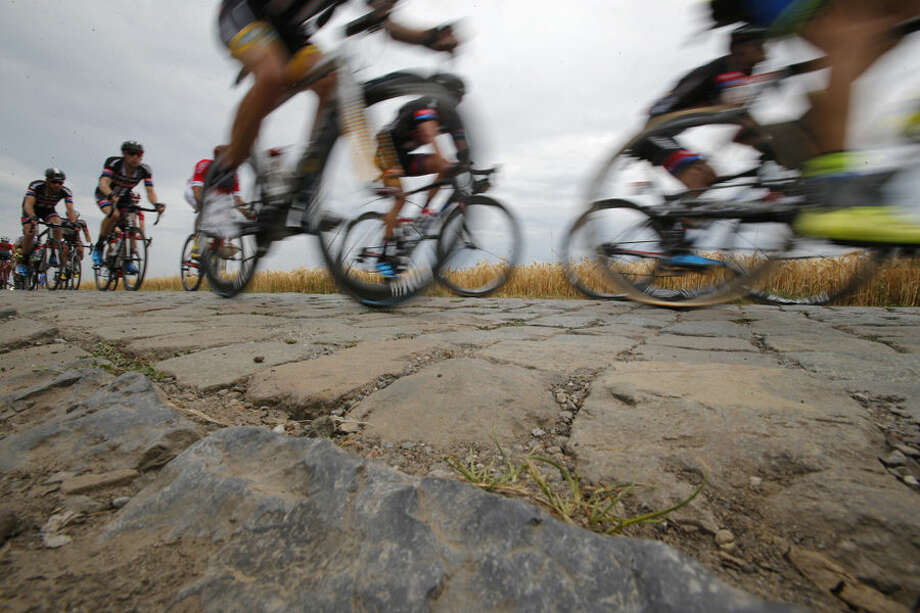 The pack passes over the first cobblestone sector near Pont-a-Celles during the fourth stage of the Tour de France cycling race over 223.5 kilometers (138.9 miles) with start in Seraing, Belgium, and finish in Cambrai, France, Tuesday, July 7, 2015. (AP Photo/Christophe Ena)
