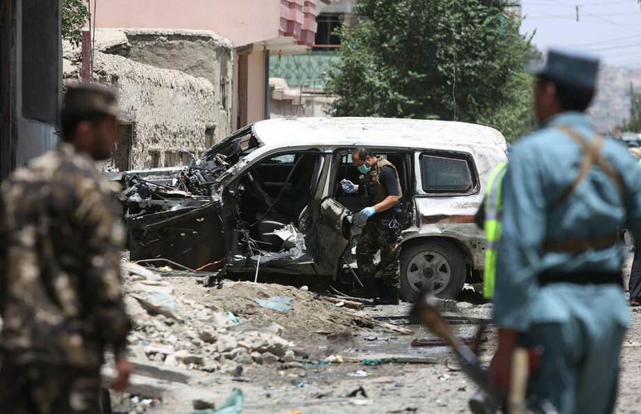 Afghan security personnel inspect a damaged vehicle at the site of a suicide attack that targeted a NATO convoy in Kabul, Afghanistan, Tuesday, July 7, 2015. An Afghan official said the attack by a suicide car bomber in the capital, Kabul, wounded at least two people. (AP Photo/Rahmat Gul)