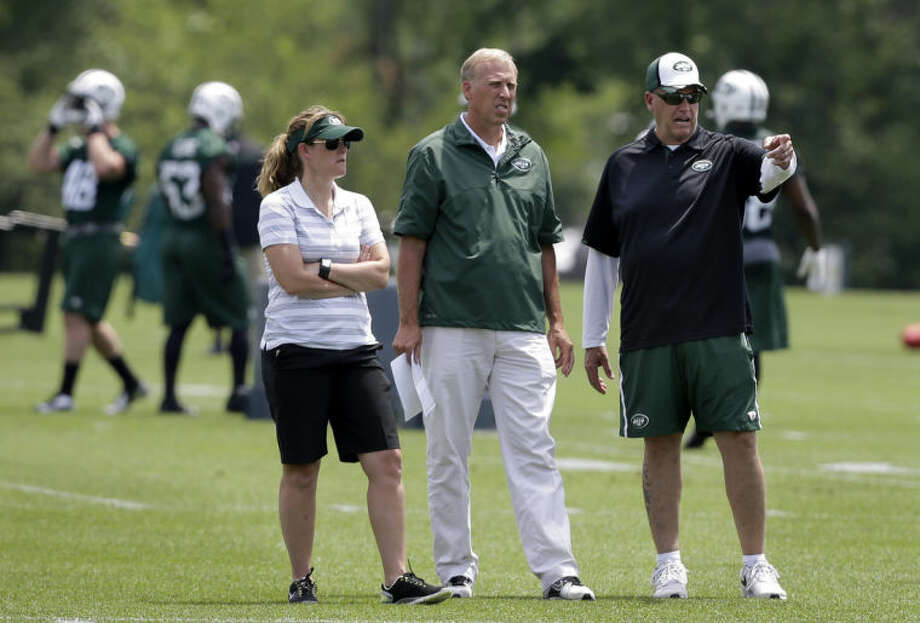 New York Jets head coach Rex Ryan, right, stands with Jets general manager John Idzik, center, as they watch during NFL football minicamp Tuesday, June 17, 2014, in Florham Park, N.J. (AP Photo/Mel Evans)