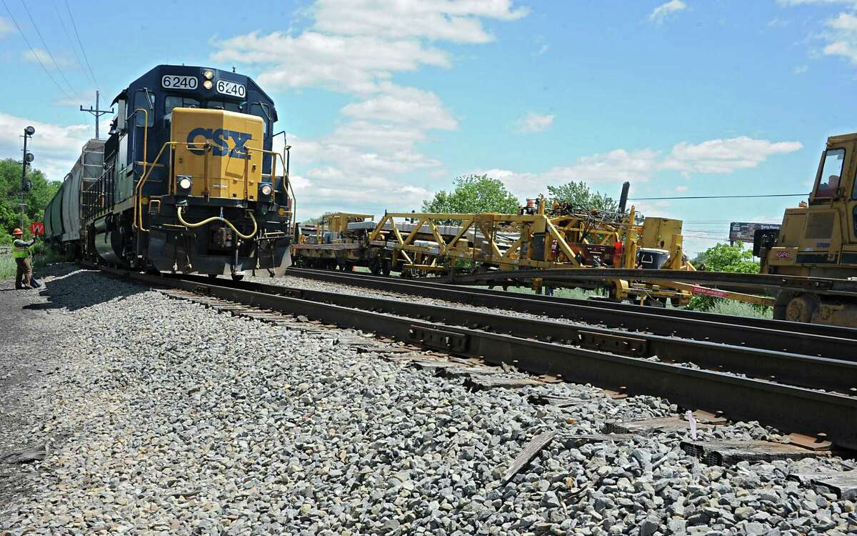 A CSX train goes by as employees from Harsco Tack Technologies work on a second rail between Albany and Schenectady near West Albany Pocket Park on Thursday, June 9, 2016 in Colonie, N.Y. Here they are dropping concrete ties onto a road bed and threading and clipping rail onto the concrete ties. (Lori Van Buren / Times Union)