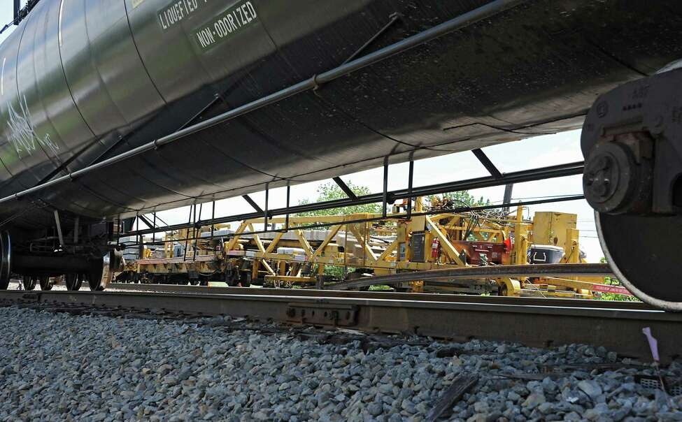 A train with oil tanks goes by employees from Harsco Tack Technologies work on a second rail between Albany and Schenectady near West Albany Pocket Park on Thursday, June 9, 2016 in Colonie, N.Y. Here they are dropping concrete ties onto a road bed and threading and clipping rail onto the concrete ties. (Lori Van Buren / Times Union)