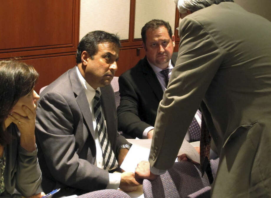 AP Photo/Dave CollinsDentist Rashmi Patel, middle, talks with his lawyer, Michael Kogut, during a hearing before the Connecticut State Dental Commission on Wednesday in Hartford. The commission is deciding if Patel's license should be reinstated, remain suspended or be revoked after one of Patel's patients died in February.