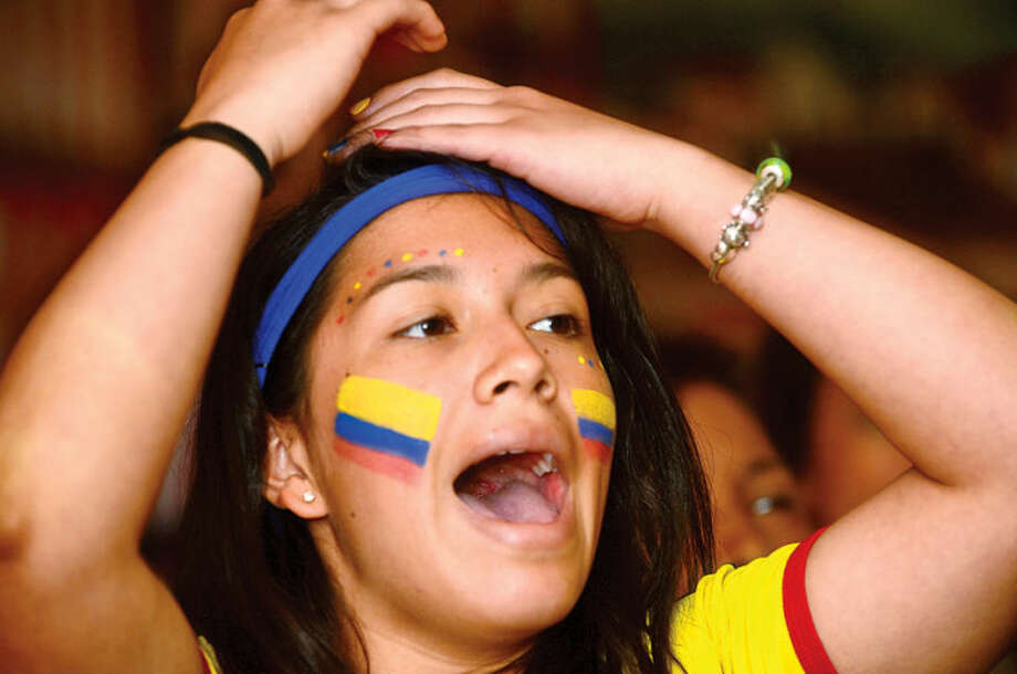 Hour photo / Erik Trautmann Patrons at La Sorpresa including Maria Fermin cheer for Colombia as they defeat Ivory Coast in their World Cup match Thursday.