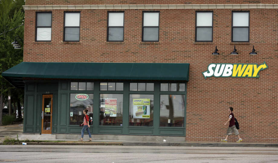 FILE - In this Tuesday, July 7, 2015, file photo, people walk past a Subway restaurant, in St. Louis. A raid at the home of Subway spokesman Jared Fogle is just the latest bad news to hit the sandwich chain. The company has been struggling with sales, its CEO is being treated for cancer and it's trying to convince customers about the quality and value of its food. (AP Photo/Jeff Roberson, File)