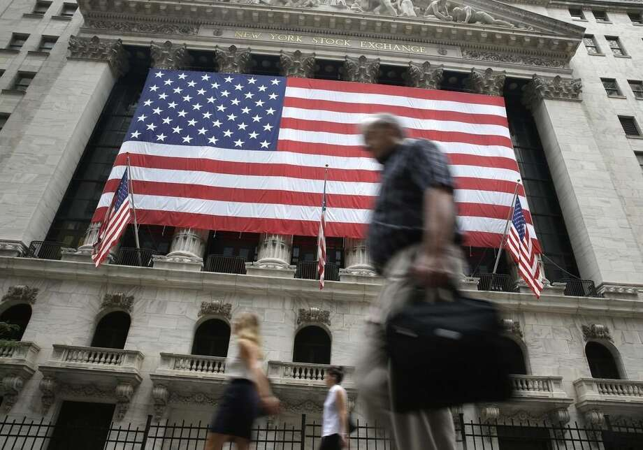 In this Wednesday, July 8, 2015 photo, people walk past the New York Stock Exchange. Growing hopes of a potential Greek bailout deal that will allow the country to stay in the euro helped European stock markets rally hard Thursday, July 9, 2015. (AP Photo/Seth Wenig)