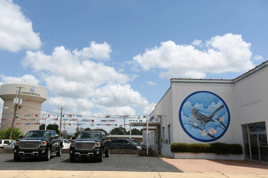 """This April 8, 2015 photo shows a """"To Kill a Mockingbird"""" mural painted on the side of a car dealership in Monroeville, Ala., the hometown of """"Mockingbird"""" author Harper Lee. Leaders are hoping more people visit the town of 6,300 people with the release of Lee's second book, """"Go Set a Watchman,"""" on July 14, 2015. (AP Photo/Sharon Steinmann)"""