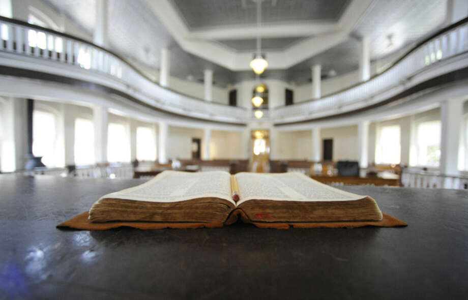 """This July 8, 2015, photo, shows a Bible opened on the judge's desk in the old Monroe County Courthouse in Monroeville, Ala. The building is a centerpiece in the hometown of """"To Kill a Mockingbird"""" author Harper Lee, whose second book """"Go Set a Watchman"""" is set for release July 14, 2015. The courtroom was used as a model for the film adaptation of """"Mockingbird."""" (AP Photo/Jay Reeves)"""