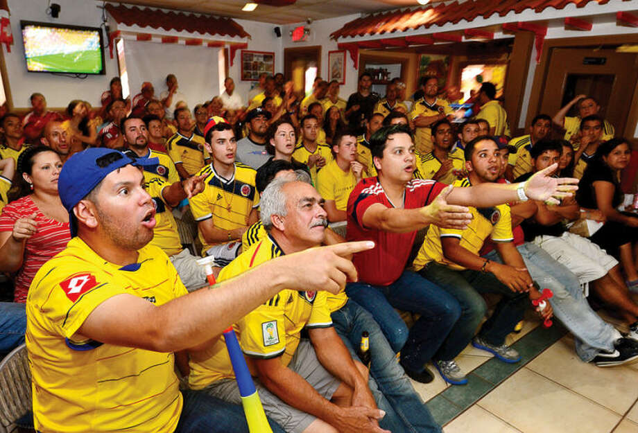Hour photo / Erik Trautmann Patrons at La Sorpresa cheer for Colombia as they defeat Ivory Coast in their World Cup match Thursday.
