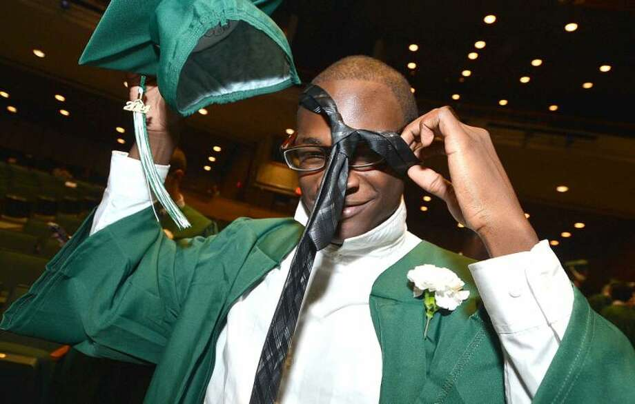 Hour Photo/Alex von Kleydorff Javaughn Henry gets a tie on that was tied by a freind for him as he gets ready to graduate with the Class of 2014 at Norwalk High School