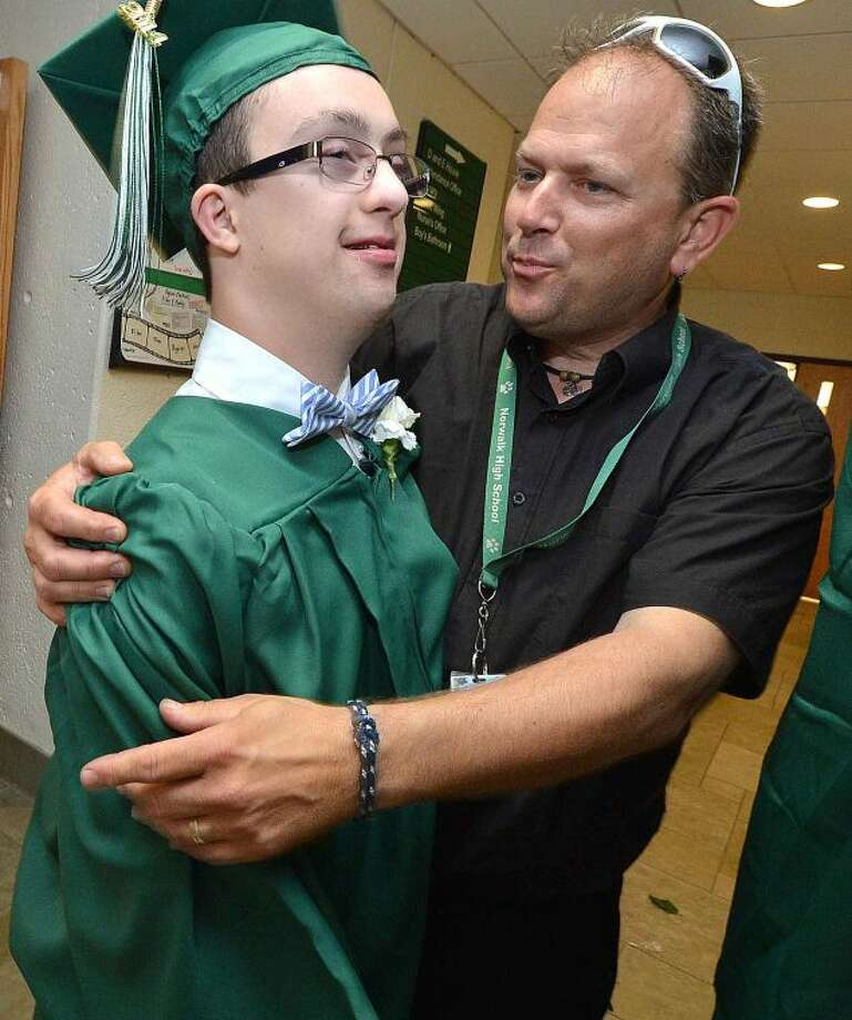 Hour Photo/Alex von Kleydorff Prom King Joey Agostino gets a hug from teacher Glenn Couture asstudents line up to graduate with the Class of 2014 at Norwalk High School