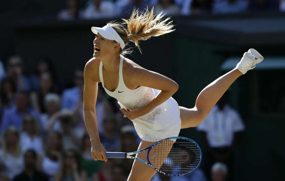 Maria Sharapova of Russia returns a shot to Serena Williams of the United States, during the women's singles semifinal match at the All England Lawn Tennis Championships in Wimbledon, London, Thursday July 9, 2015. (AP Photo/Alastair Grant)