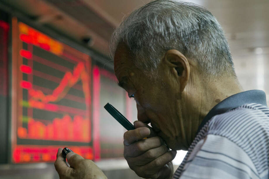 A Chinese investor uses a magnifying glass to look at his mobile phone screen as he monitors stock prices at a brokerage house in Beijing, China, Thursday, July 9, 2015. Asian stock markets continued to react on Thursday as the Chinese government took measures aimed at stabilizing the market. (AP Photo/Ng Han Guan)