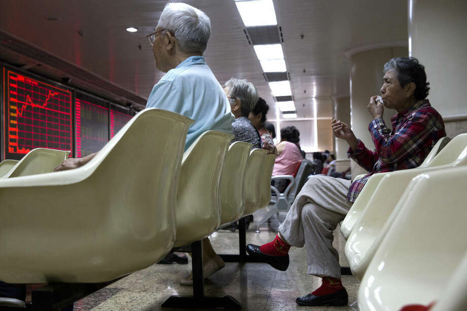Chinese investors monitor stock prices at a brokerage house in Beijing, China, Thursday, July 9, 2015. Asian stock markets continued to react on Thursday as the Chinese government took measures aimed at stabilizing the market. (AP Photo/Ng Han Guan)