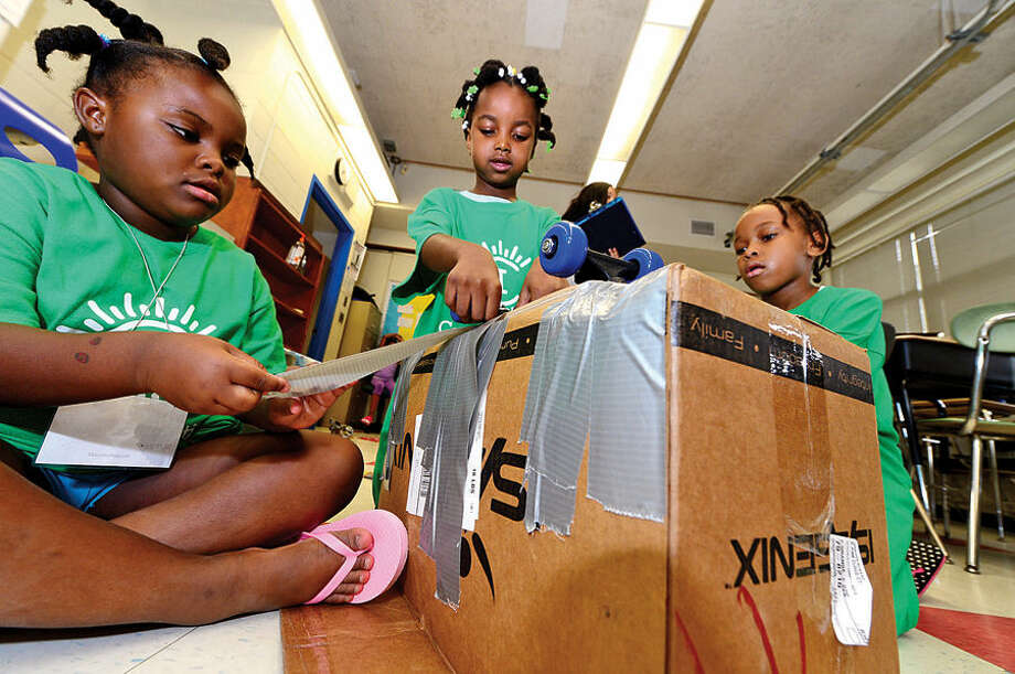 Hour photo / Erik Trautmann Glory-Anne Jean-Marie, Jasmine Sinclair and Sophia Joseph build a cart out of scrap materials in the Kartwheel module as Amazing Girls Science hosts a Camp Invention workshop for girls in grades 1 to 6 Thursday at Nathan Hale Middle School.