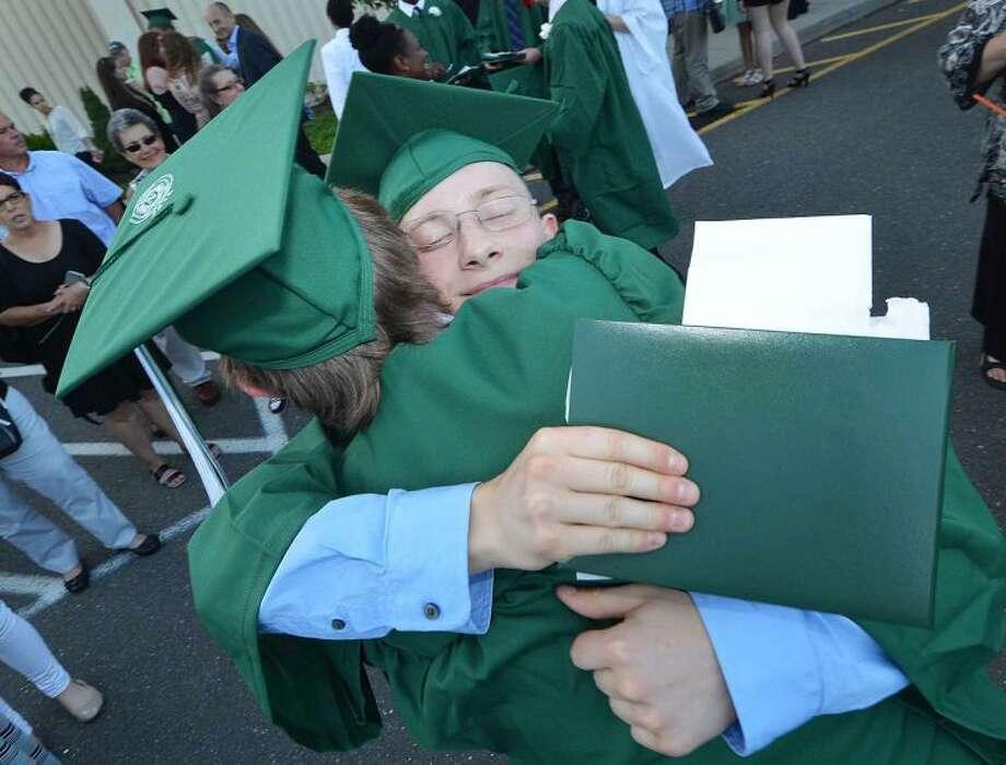 Hour Photo/Alex von Kleydorff Gavin Schuerch gets a hug from friend Kevin Garrish during graduation with the Norwalk High School Class of 2014