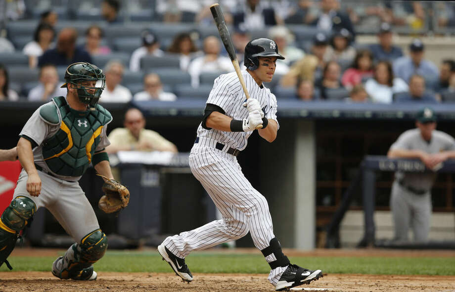 New York Yankees' Jacoby Ellsbury hits a fourth-inning, two-run single in a baseball game against the Oakland Athletics at Yankee Stadium, Thursday, July 9, 2015, in New York. (AP Photo/Kathy Willens)