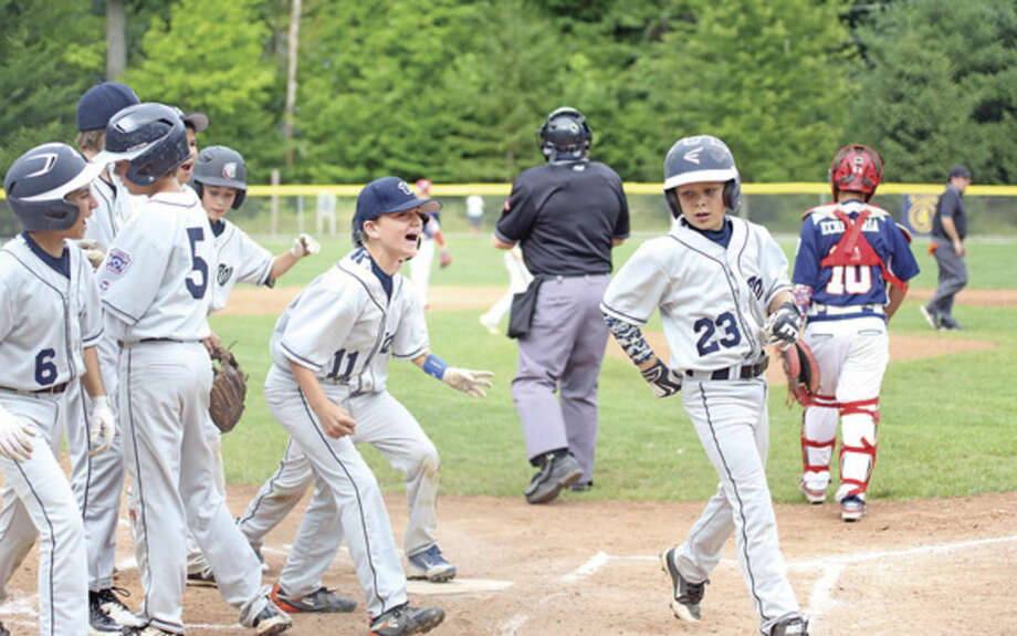Photo by Danielle CallowayWilton's Ryan van Heyst (23) is cheered on by teammates after scoring on a solo home run in the first inning of Monday's 10-11-year-old District 1 Little League playoff game against Norwalk at Bisceglie Field in Weston. Wilton lost to Norwalk 19-4.