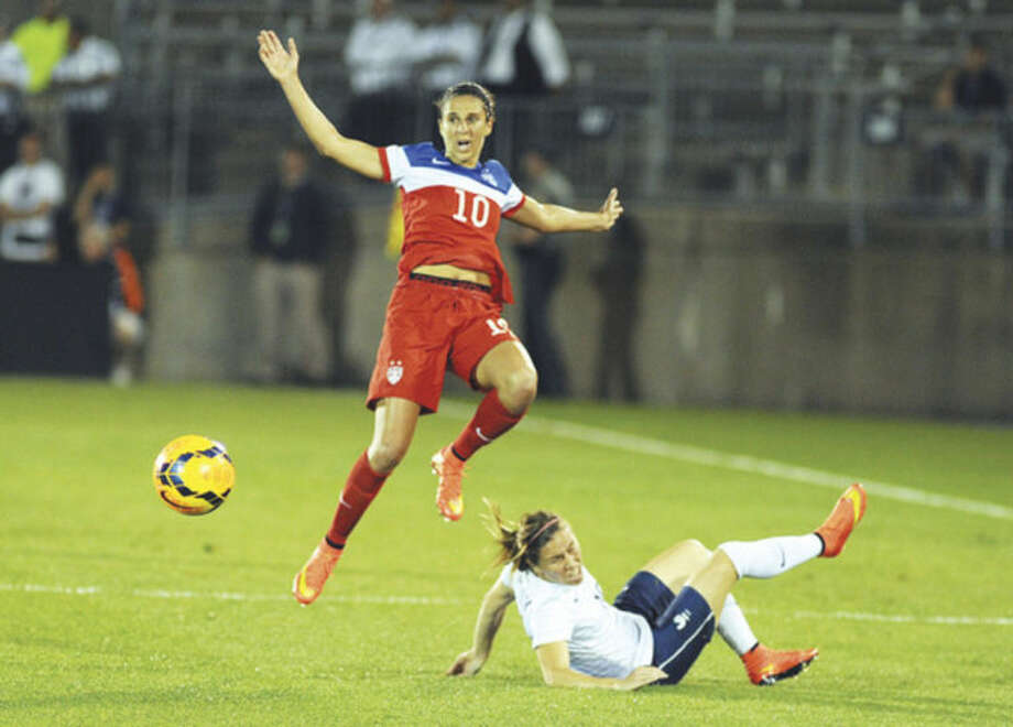 Hour photo/John NashTeam USA's Carli Lloyd, left, leaps over France's Camille Abily during second half action of Thursday night's international friendly at Rentschler Field in East Hartford. The squads battled to a 2-2 tie.