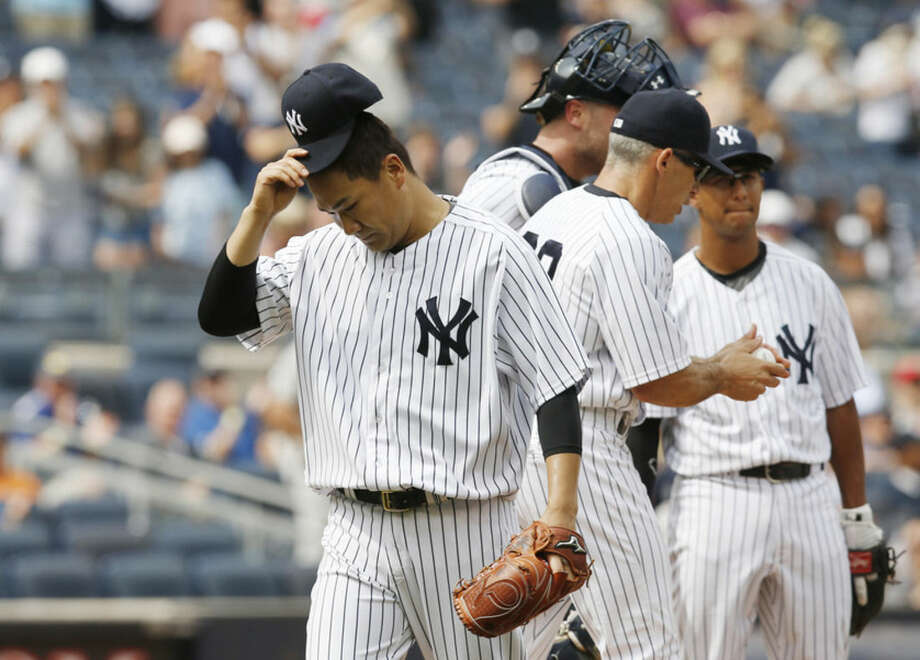 New York Yankees starting pitcher Masahiro Tanaka, left, tips his cap as he leaves the mound after New York Yankees manager Joe Girardi, center, took Tanaka out after he had pitched seven and two-thirds innings in a baseball game against the Oakland Athletics at Yankee Stadium in New York, Thursday, July 9, 2015. (AP Photo/Kathy Willens)