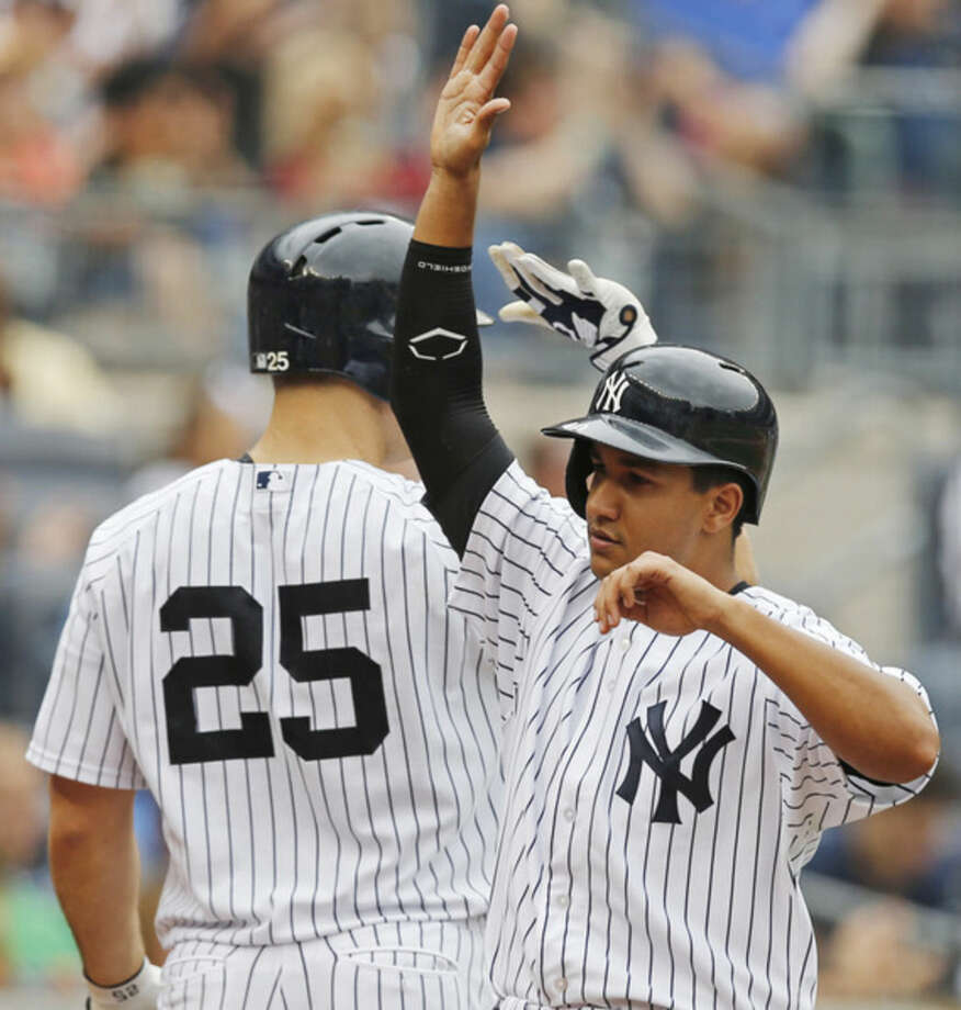 New York Yankees' Cole Figueroa, right, celebrates with New York Yankees designated hitter Mark Teixeira (25) after scoring on Jacoby Ellsbury's fourth-inning, two-run single in a baseball game against the Oakland Athletics at Yankee Stadium in New York, Thursday, July 9, 2015. (AP Photo/Kathy Willens)