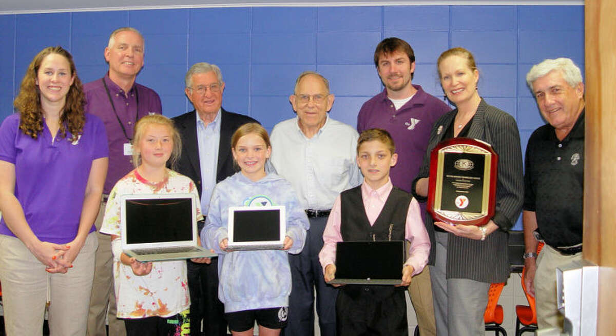 Children in the Y's Afterschool Child Care Program were treated to a roomful of new computer equipment, courtesy of the Wilton Kiwanis Club. Pictured left to right in front are Mairead Kehoe, 11; Hailey Looney, 10; and Alex Klanko, 10. Behind them are: Y Afterschool Director Laura Koellmer, Y Executive Director Bob McDowell, incoming Kiwanis President Paul Hannah, Kiwanis Contributions Committee Chairman Jerry Holdridge, Y Afterschool Director Geoff Malyszka, Kiwanis President Nancy Pantoliano holding the new recognition plaque for the room, and Y Board President Howard Steinberg.