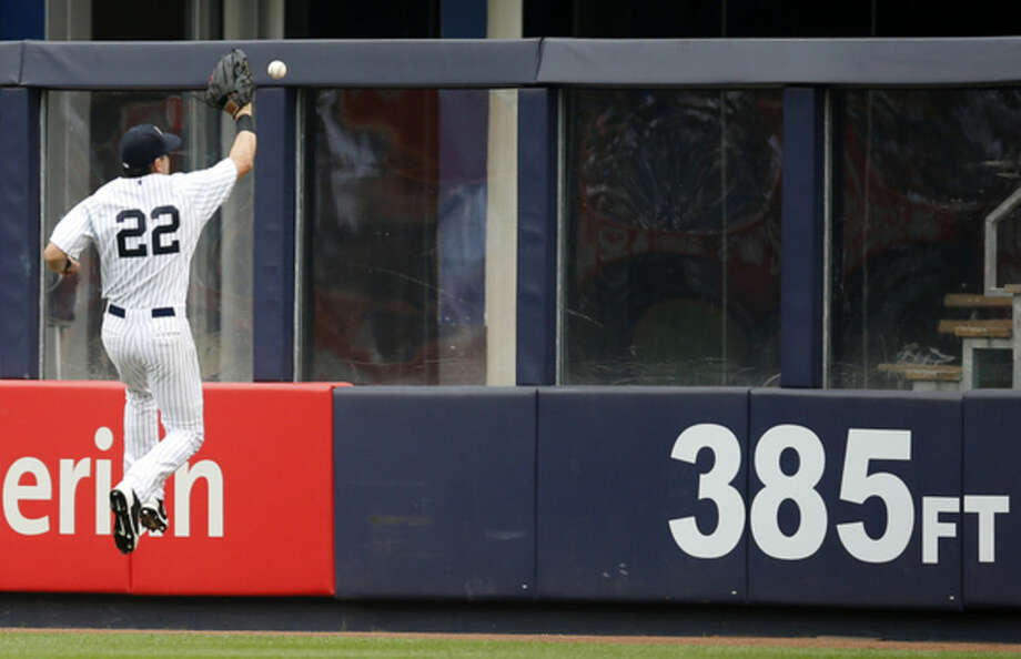 New York Yankees center fielder Jacoby Ellsbury (22) leaps on the outfield wall fielding Mark Canha's second-inning, RBI double in a baseball game against the Oakland Athletics at Yankee Stadium in New York, Thursday, July 9, 2015. (AP Photo/Kathy Willens)