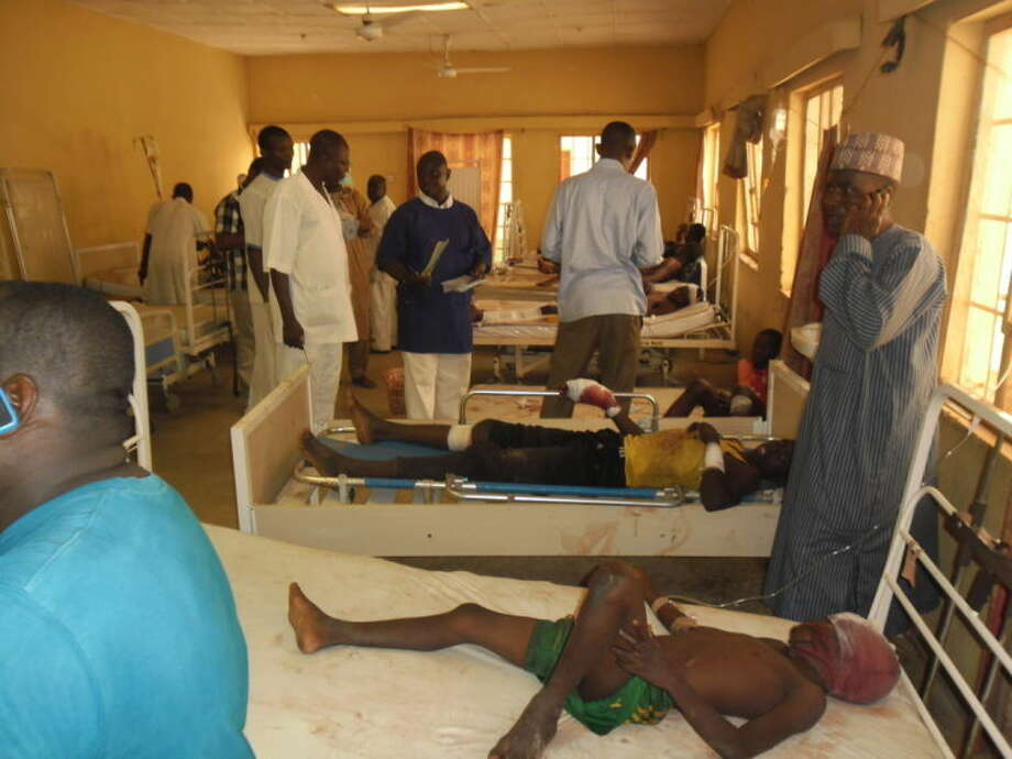 "Victims of a suicide bomb explosion at a World Cup viewing center receive treatment at Sani Abacha specialist hospital in Damaturu, Nigeria, Wednesday, June 18, 2014. An explosion at an illegal World Cup viewing site in Damaturu northeast Nigeria killed at least 14 people while security forces arrested a ""terror kingpin"" among nearly 500 people detained as suspected terrorists in the southeast of the country, in another signal that Nigeria's Islamic uprising is spreading. Police said at least 26 people were wounded in Tuesday night's blast as soccer fans were viewing the Brazil-Mexico match in Damaturu, capital of Yobe state. (AP Photo/Adamu Adamu)"