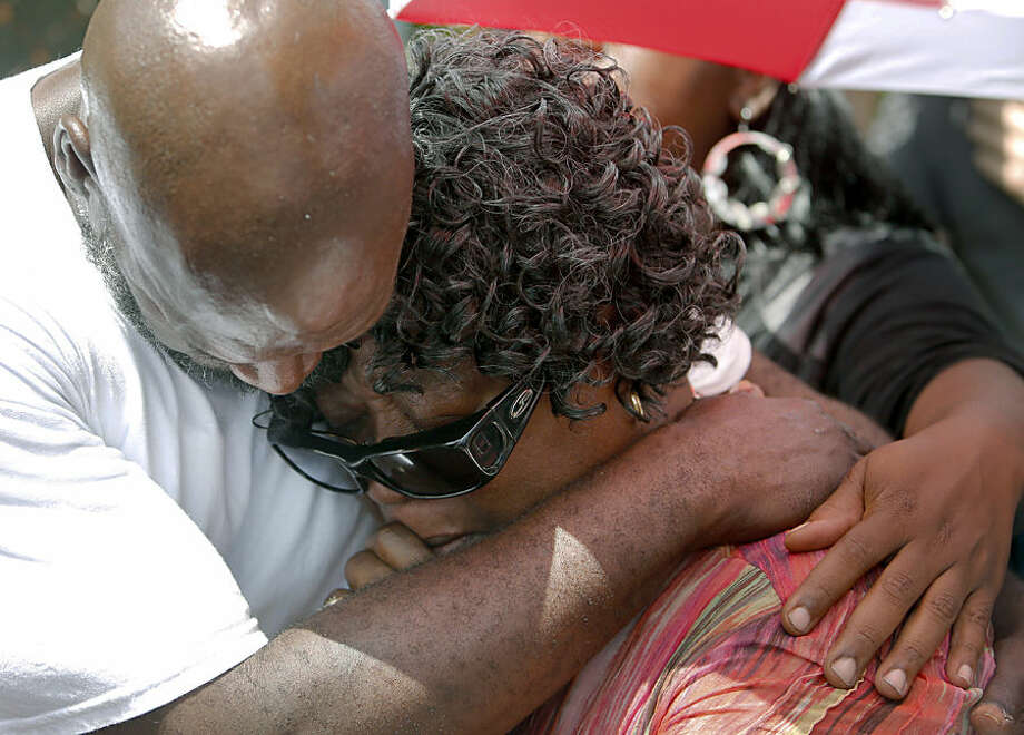 Judy Scott, right, is comforted by Alfred Smalls on Thursday, July 9, 2015, at the site in North Charleston, S.C., where her son, Walter Scott, was shot and killed by North Charleston police officer Michael Slager on April 4. Family attorney Chris Stewart says Judy Scott was unable to find words to describe her feelings during her first visit to the site. (AP Photo/Mic Smith)