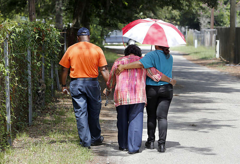 Anthony Scott, left, walks away Thursday, July 9, 2015, with his mother, Judy Scott, center, and her granddaughter Samantha Scott from the site in North Charleston, S.C. where Judy Scott's son, Walter Scott, was shot and killed by North Charleston police officer Michael Slager on April 4, in North Charleston, S.C. This was Judy Scott's first visit to site. (AP Photo/Mic Smith)