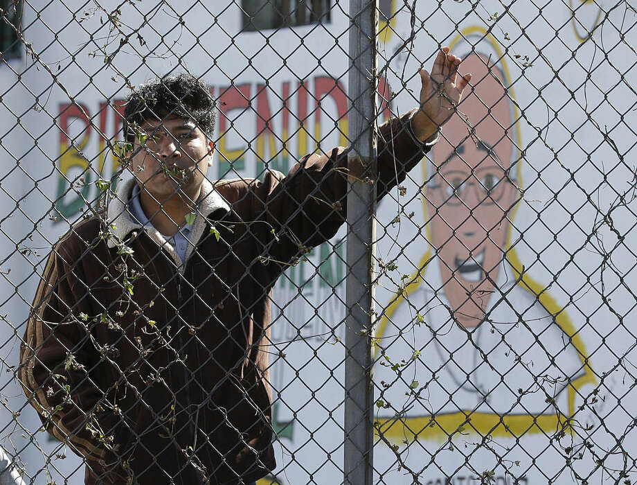 """An inmate stands behind the fence at Palmasola prison, decorated with a mural of Pope Francis that reads in Spanish: """"Welcome who comes in the name of the Lord"""" as the pontiff leaves after visiting prisoners in Santa Cruz, Bolivia, Friday, July 10, 2015. The pope urged inmates at the notoriously violent prison to not despair as he wrapped up his visit to Bolivia with a message of hope and solidarity for those caught up in Bolivia's corrupt law enforcement system. (AP Photo/Gregorio Borgia)"""